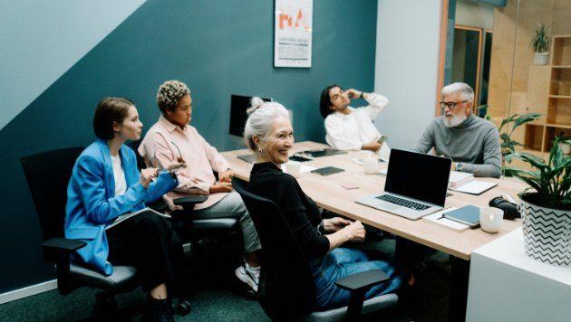 Frauen und Männder in einem Büro sitzen an einem Konferenzwisch.