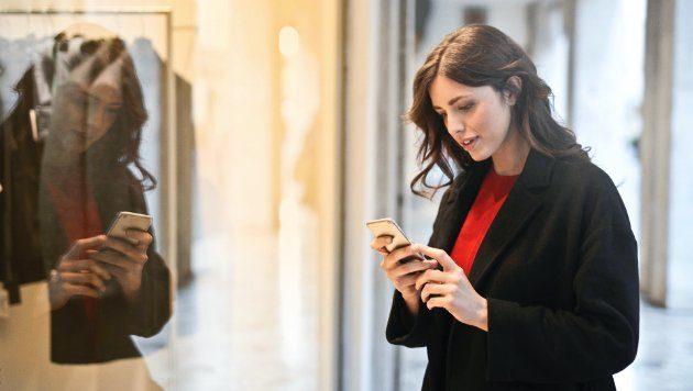 Bild einer Frau in einem Geschäft mit Smartphone in der Hand.